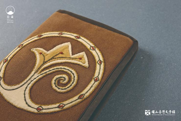 這本2007年的行事曆兼筆記,包覆木褐色的布書套,封面繡紋像百合,也像山脈。(藏品/霍斯陸曼・伐伐提供,圖/國立臺灣文學館)